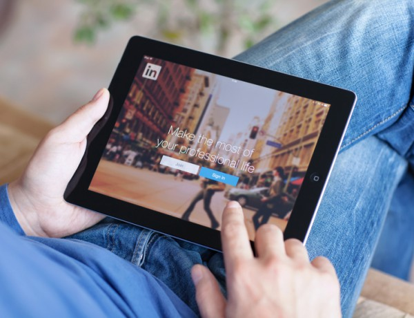 Man holding iPad with App LinkedIn on the screen